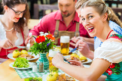 People in bavarian Tracht eating in restaurant or pub. Young people in traditional Bavarian Tracht eating pork in restaurant or pub for lunch or dinner Stock Photo