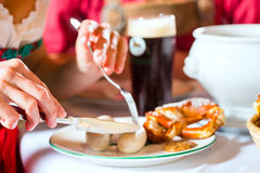 People in Bavarian Tracht eating in restaurant or pub. Young people in traditional Bavarian Tracht eating with sausages in restaurant or pub lunch or dinner Royalty Free Stock Photography