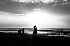 People in the beach. Couple walking in the beach and hods each other hands and other people enjoying the sunset Stock Photo