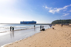 People on beach as ship enters harbor Stock Photo
