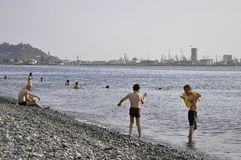 PEOPLE ON THE BEACH OF BATUMI  IN THE BACKGROUND  BATUMI HARBOUR Stock Photos