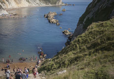 People on the beach and the blue waters of Durdle Door. The picture shows some blue, shiny waters and people sunbathing in Durdle Door, Dorset, England. It was Royalty Free Stock Photo