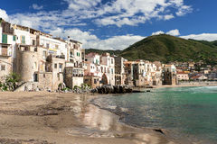 People at beach in Cefalu at spring time. CEFALU, ITALY - APRIL 17, 2014: CEFALU, ITALY - AUGUST 23: Unidentified people at beach in Cefalu, Sicily, Italy Stock Photography