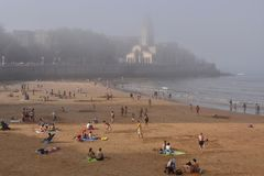 People on the beach foggy day in Gijon Spain stock photography