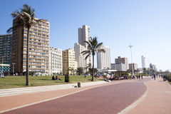 People on Beach Front Promenade Against City Skyline Stock Photo