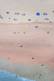 People on a beach from high above. Some people on a beach photographed from high above on a bright day Stock Photo