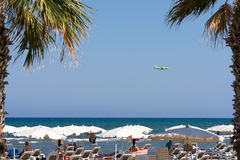 People on beach and landing plane. Royalty Free Stock Image
