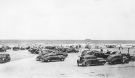 People At The Beach Late 1940s. Horizontal black and white photo of people and cars at the beach in the late 1940s stock photo