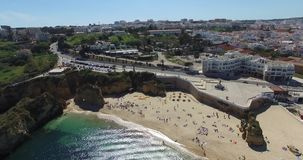 People on beach near cliffs Lagos aerial view stock video footage