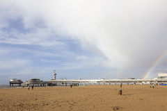 People on beach near scheveningen pier with cloudy sky and rainb Royalty Free Stock Photos