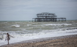 People on the beach, the old pier in Brighton on a sunny day. Stock Image