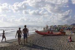 People on the beach shoreline at sunset light in Versilia. MARINA DI MASSA, ITALY - AUGUSt 17 2015: People on the beach shoreline at sunset light in Versilia Stock Image