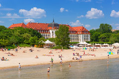 People on the beach of Sopot, Poland. SOPOT, POLAND - 7 JUNE: People on the beach of Sopot at the Grand Hotel on 7 June 2014. Grand hotel built in 1924-1927 is Royalty Free Stock Images