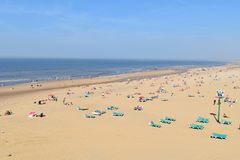 People on the beach in the summer. People on the beach and beach chairs in the summer time at Scheveningen, Netherlands Royalty Free Stock Image