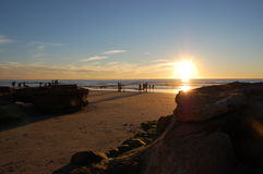 People on the beach at sunset. Pacific ocean Stock Photos