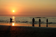 People on beach at sunset Stock Photo