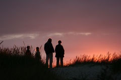 People on beach at sunset Stock Images