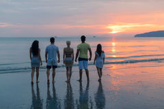 People On Beach At Sunset Back Rear View, Young Tourist Group Walking On Sea In Evening. While Summer Vacation royalty free stock image