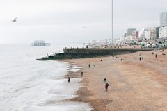 People on the beach and West Pier at Brighton, UK. People on the beach and West Pier at Brighton, the most popular seaside destination in the UK for overseas Royalty Free Stock Photography