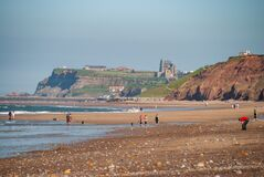 People on the beach at Whitby with the abbey on the cliffs in the background