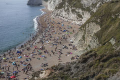 People on the beach and the white cliffs of Durdle Door. The picture shows some blue, shiny waters and people sunbathing and having fu in Durdle Door, Dorset Stock Images