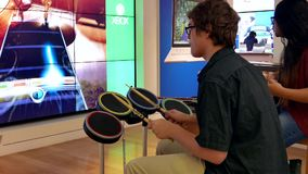 People beating a drum and playing a guitar with Microsoft demonstrated game stock footage