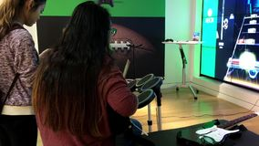 People beating a drum and playing a guitar with Microsoft demonstrated game stock video footage