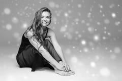 People Beautiful woman body on floor winter snow black and white. Studio shot stock photos