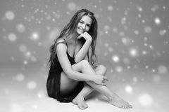 People Beautiful woman body on floor winter snow black and white. Studio shot Royalty Free Stock Photo