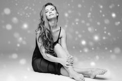People Beautiful woman body on floor winter snow black and white. Studio shot Royalty Free Stock Photography