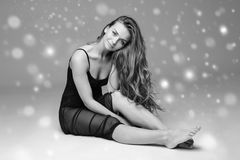 People Beautiful woman body on floor winter snow black and white. Studio shot Royalty Free Stock Photos
