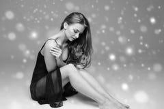 People Beautiful woman body on floor winter snow black and white. Studio shot stock image