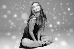 People Beautiful woman body on floor winter snow black and white. Studio shot stock photography