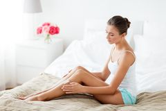 Beautiful woman applying cream to her legs at home. People, beauty, cosmetics, bodycare and spa concept - beautiful woman applying moisturizing cream to her legs Royalty Free Stock Image