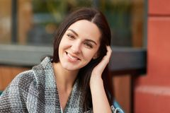 People, beauty, emotions and lifestyle concept. Close up portrait of brunette female with appealing look, enjoys calm peaceful atm. Osphere in cozy outdoor stock images