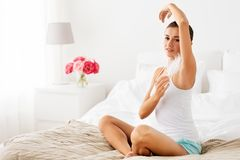 Woman with feather touching her armpit at home royalty free stock image