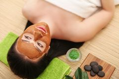 People, beauty, spa, cosmetology and skincare concept - close up of beautiful young woman lying with closed eyes and cosmetologist. Applying facial mask by Stock Photography