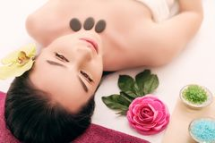 People, beauty, spa, cosmetology and skincare concept - close up of beautiful young woman lying with closed eyes and cosmetologist. Applying facial mask by Royalty Free Stock Photos