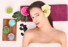 People, beauty, spa, cosmetology and skincare concept - close up of beautiful young woman lying with closed eyes and cosmetologist. Applying facial mask by Royalty Free Stock Photo