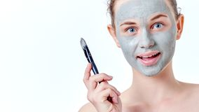 People, beauty, spa, cosmetology and skincare concept. Young teenage girl applying facial mask using brush. stock images