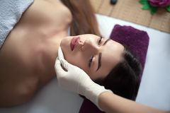 People, beauty, spa, healthy lifestyle and relaxation concept - close up of beautiful young woman lying with closed eyes and havin Stock Image