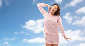 Happy young woman in pajama stretching over sky royalty free stock image