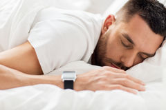 Close up of man with smartwatch sleeping in bed Royalty Free Stock Photo
