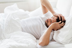 Man in bed at home suffering from headache Stock Photography