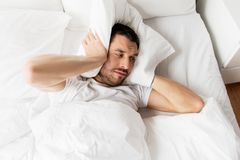 Man in bed with pillow suffering from noise. People, bedtime and rest concept - man lying in bed with pillow suffering from noise at home stock images