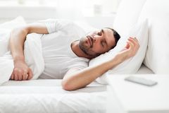 Man sleeping in bed with smartphone on nightstand. People, bedtime and rest concept - man sleeping in bed at home with smartphone on nightstand Royalty Free Stock Photo
