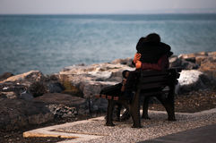 People in bench by the sea Stock Photography