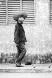 People in Benin, in black and white. PORTO-NOVO, BENIN - MAR 10, 2012: Unidentified Beninese man walks with a stuff on his head. People of Benin suffer of royalty free stock images