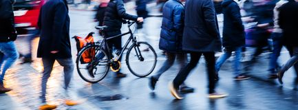 People and bicycle crossing a city street at dusk Stock Photography