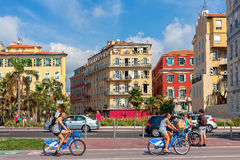People on bicycles and colorful buildings of Nice on background. Stock Photo
